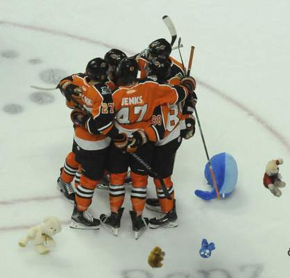 Justin A. Cohn | The Journal Gazette  A.J. Jenks, just after scoring, celebrates with Komets teammates as stuffed animals rain down from the stands at Memorial Coliseum as part of the annual Teddy Bear Toss.