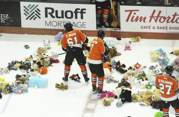 Justin A. Cohn | The Journal Gazette Komets players Taylor Ross, Brycen Martin and Shawn Szydlowski help clean up the ice after the annual Teddy Bear Toss on Friday.