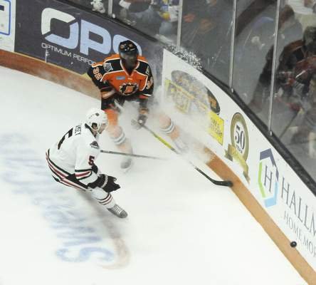 Justin A. Cohn | The Journal Gazette  Komets forward Jermaine Loewen, top, flicks the puck around the boards while spraying ice at Memorial Coliseum with the Indy Fuel's Jack Ramsey defending.