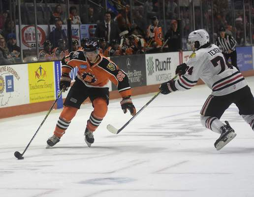 Katie Fyfe | The Journal Gazette  The Komets' Olivier Galipeau carries the puck while the Indy Fuel's Keoni Texeira defends during the second period at Memorial Coliseum on Friday.