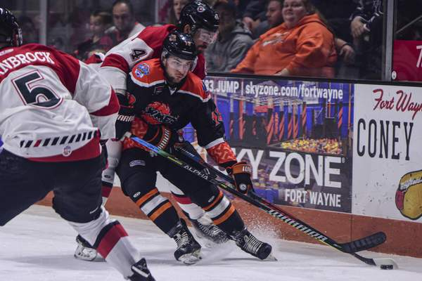 Mike Moore | The Journal Gazette Komets forward Anthony Petruzzelli controls the puck while colliding with Cyclones' defenseman Kurt Gosselin in the first period at Memorial Coliseum on Saturday.