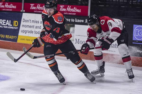 Mike Moore | The Journal Gazette Komets forward Anthony Petruzzelli controls the puck while Cyclones' forward Nate Mitton makes a move in the first period at Memorial Coliseum on Saturday.