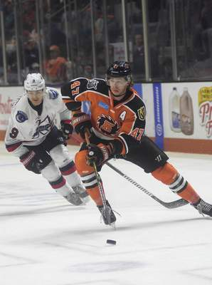 Katie Fyfe | The Journal Gazette  Komets' A.J. Jenks chases the puck while Kalamazoo Wings Zach Diamantoni follows close behind during the third period at Memorial Coliseum on Sunday.