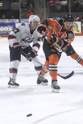 Katie Fyfe | The Journal Gazette  Komets' A.J. Jenks shoots the puck during the first period against Kalamazoo Wings at Memorial Coliseum on Sunday.