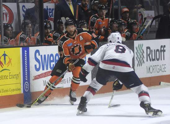 Katie Fyfe | The Journal Gazette  Komets' Shawn Szydlowski looks to pass the puck while Kalamazoo Wings Ian Edmondson tries to stop him during the second period at Memorial Coliseum on Sunday.