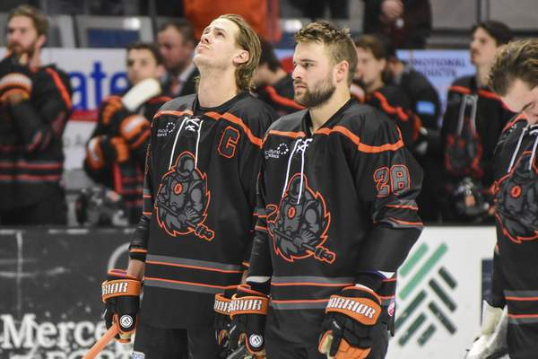 Mike Moore | The Journal Gazette Komets forward A.J. Jenks, left stands with teammate forward Matthew Boudens during the National Anthem before the game against Toledo at Memorial Coliseum on Tuesday.