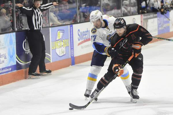 Mike Moore | The Journal Gazette Komets forward Shawn Szydlowski and Walleye forward T.J. Hensick fight for possession of the puck in the first period at Memorial Coliseum on Tuesday.