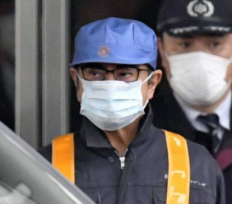 FILE - In this March 6, 2019, file photo, a masked man, front with blue cap, believed to be former Nissan Chairman Carlos Ghosn, leaves Tokyo's Detention Center in Tokyo. (Yu Nakajima/Kyodo News via AP, File)