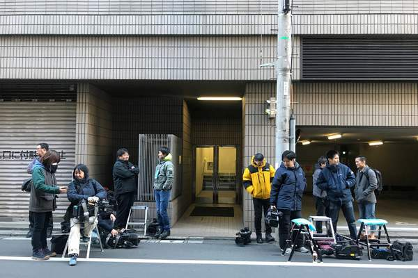 Journalists stake out at the back entrance of a building which houses an office of Junichiro Hironaka, a lawyer for Nissan's former Chairman Carlos Ghosn, in Tokyo Tuesday, Dec. 31, 2019. (AP Photo/Richard Colombo)