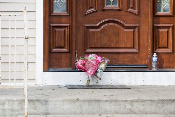 Julius Constantine Motal | Associated Press Flower bouquets rest on the doorstep of a rabbi's residence in Monsey, N.Y., Sunday, following a stabbing Saturday night during a Hanukkah celebration.