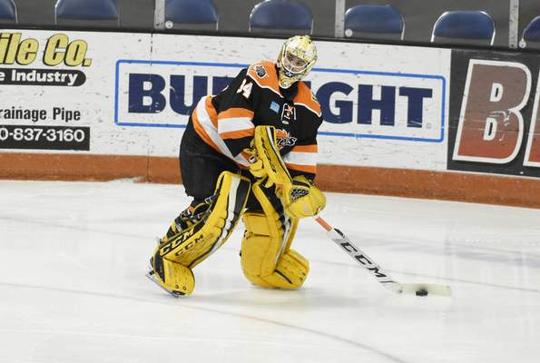 Rachel Von Stroup | The Journal Gazette  Komets' goalie Patrick Munsonpasses the puck during the first period against the Kalamazoo Wings at the Memorial Coliseum on Saturday night.
