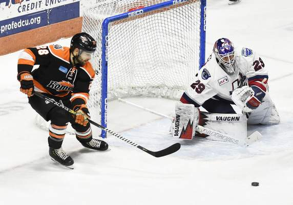 Rachel Von Stroup | The Journal Gazette  The Komets' Matthew Boudens tries to direct the puck as Wings' goalie Jake Hildebrand guards the net during the first period at Memorial Coliseum on Saturday night.