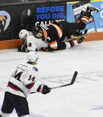 Rachel Von Stroup | The Journal Gazette  The Komets' Chase Stewart tackles the Wings' Justin Taylor in the first period at Memorial Coliseum on Saturday night.