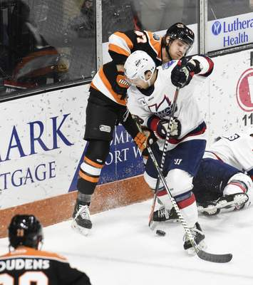 Rachel Von Stroup | The Journal Gazette  The Komets' A.J. Jenks fights for the puck during the first period against the Kalamazoo Wings at Memorial Coliseum on Saturday night.