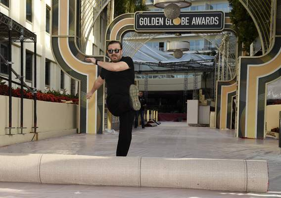 Ricky Gervais, host of this Sunday's 77th annual Golden Globe Awards, kicks out the red carpet during Preview Day for the Globes at the Beverly Hilton, Friday, Jan. 3, 2020, in Beverly Hills, Calif. (AP Photo/Chris Pizzello)