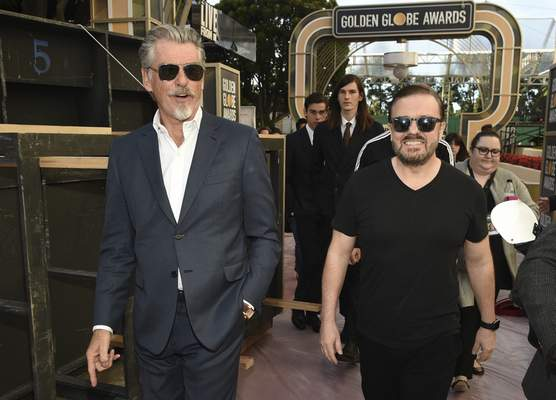 Ricky Gervais, right, host of Sunday's 77th Annual Golden Globe Awards, mingles with actor Pierce Brosnan during Preview Day for the Globes at the Beverly Hilton, Friday, Jan. 3, 2020, in Beverly Hills, Calif. Brosnan's sons Paris and Dylan, seen in the middle background left to right, are serving as Golden Globe Ambassadors this year. (AP Photo/Chris Pizzello)
