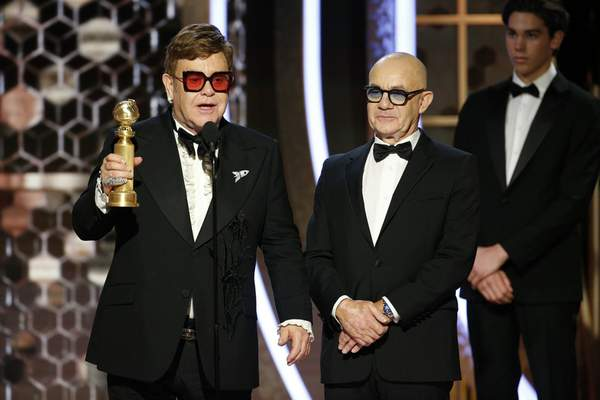 This image released by NBC shows Elton John, left, and Bernie Taupin accepting the award for best original song for