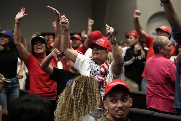 Supporters of President Donald Trump turn and yell towards the news media during a rally for evangelical supporters at the King Jesus International Ministry, Friday, Jan. 3, 2020, in Miami. (AP Photo/Lynne Sladky)