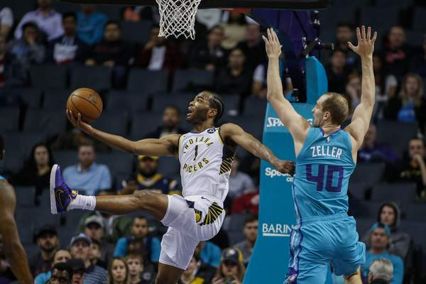 Associated Press Pacers forward T.J. Warrenputs up a shot around the defense of Hornets forward Cody Zeller during the first half of Monday's game in Charlotte, N.C. Warren finished the game with 36 points.