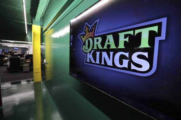 FILE - In this May 2, 2019, file photo, the DraftKings logo is displayed at the sports betting company headquarters in Boston. DraftKings is reviewing a former