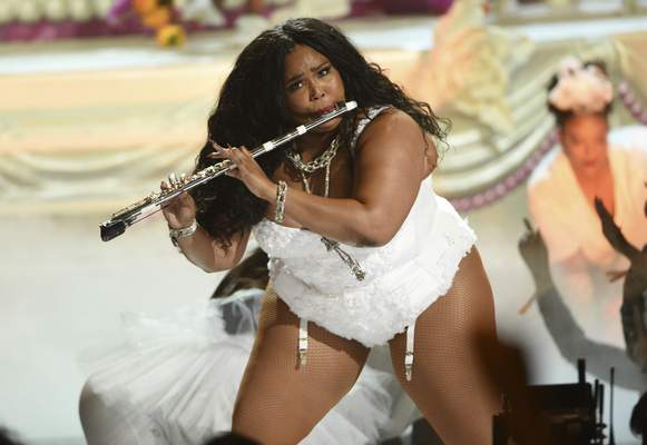 FILE - This June 23, 2019 file photo shows Lizzo playing the flute at the BET Awards in Los Angeles. Billie Eilish and Lizzo, both nominated for the top four prizes at the Grammy Awards, are slated to perform at the Grammy Awards on Jan. 26 event, airing live on CBS. (Photo by Chris Pizzello/Invision/AP, File)