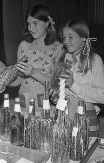 May 1, 1970: Kay Mettert, left, and Erin Smith sell empty liquor bottles that were taken home by Hillcrest School students and decorated to raise money for a trip to Chicago. (Journal Gazette file)