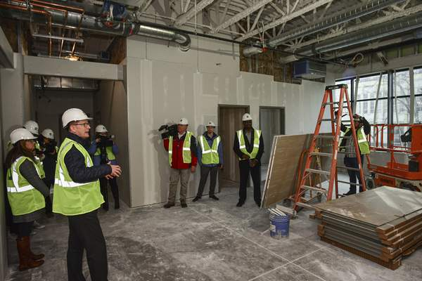 Mike Moore | The Journal Gazette Sam Hardy, left, chief operations officer of the Rescue Mission, leads a tour Thursday of the new facility on East Washington Boulevard.