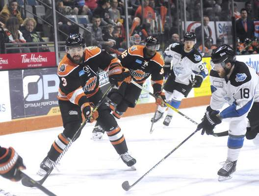 Katie Fyfe | The Journal Gazette  The Komets' Chase Stewart hits the puck while Idaho's A.J. White defends him during the second period at Memorial Coliseum on Friday.