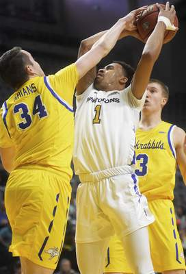 Katie Fyfe | The Journal Gazette  PFW Mastodons' sophomore Jarred Godfrey shoots the ball but gets blocked by South Dakota State sophomore Alex Arians during the second half at Memorial Coliseum on Saturday.