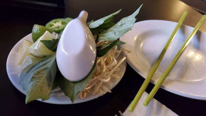 Fresh herbs, sprouts and limes -- the traditional garnishes -- come with most pho soups at Saigon Vietnamese restaurant on South Calhoun Street.