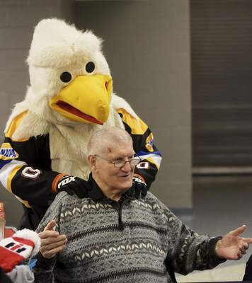 Katie Fyfe | The Journal Gazette  Icy D Eagle gives Komets Hall of Famer George Drysdale a shoulder rub during the Harvester Homecoming Night with the Komets at the Allen County War Memorial Coliseum on Sunday, Jan. 12, 2020.