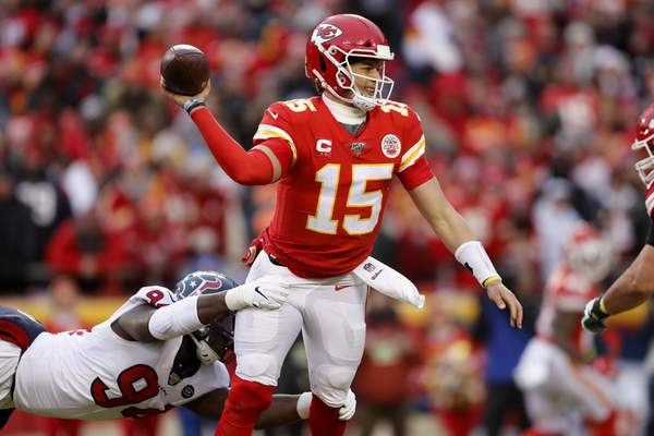 Kansas City Chiefs quarterback Patrick Mahomes (15) throws under pressure from Houston Texans defensive end Charles Omenihu (94) during the first half of an NFL divisional playoff football game, in Kansas City, Mo., Sunday, Jan. 12, 2020. (AP Photo/Jeff Roberson)