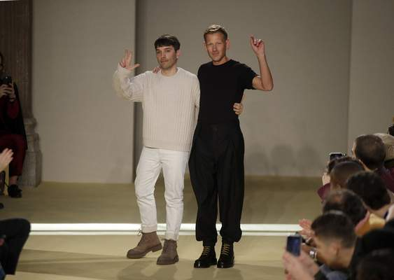 Creative director Paul Andrew, right, accept applause flanked by menswear designer Guillaume Meilland, at the conclusion of the the Salvatore Ferragamo men's Fall-Winter 2020/21 fashion show, that was presented during the fashion week, in Milan, Italy, Sunday, Jan. 12, 2020. (AP Photo/Luca Bruno)