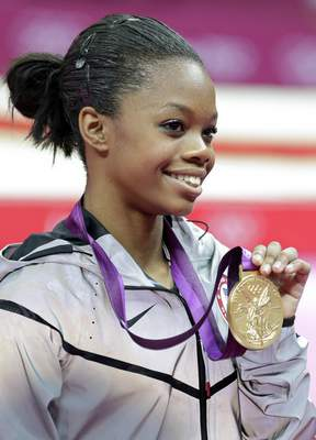 FILE - This Aug. 2, 2012 file photo shows U.S. gymnast Gabrielle Douglas displaying her gold medal during the artistic gymnastics women's individual all-around competition at the 2012 Summer Olympics in London. (AP Photo/Gregory Bull, File)