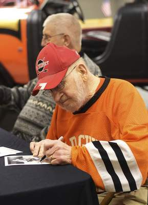 Katie Fyfe | The Journal Gazette  Komets Hall of Famer Mr. Komet Eddie Long signs his autograph for a fan during the Harvester Homecoming Night with the Komets at the Allen County War Memorial Coliseum on Sunday, Jan. 12, 2020.