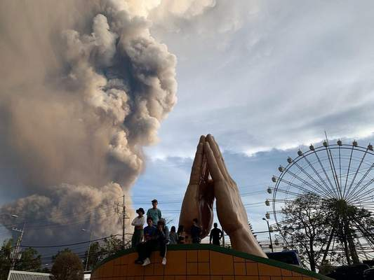 Associated Press People watch as the Taal volcano spews ash and smoke during an eruption in Tagaytay, Cavite province south of Manila, Philippines, on Sunday. The eruption closed Manila's international airport.