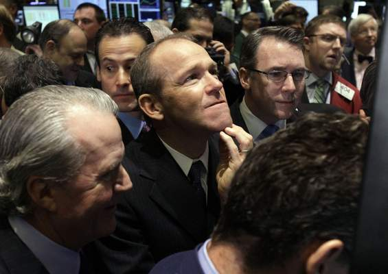 FILE - In this Jan. 26, 2011 file photo, Nielsen Company CEO David Calhoun, center, watches progress as he waits for the company's IPO to begin trading, on the floor of the New York Stock Exchange. (AP Photo/Richard Drew, File)
