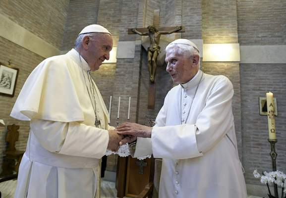 FILE - In this June 28, 2017, file photo, Pope Francis, left, and Pope Benedict XVI, meet each other on the occasion of the elevation of five new cardinals at the Vatican. (L'Osservatore Romano/Pool photo via AP, File)