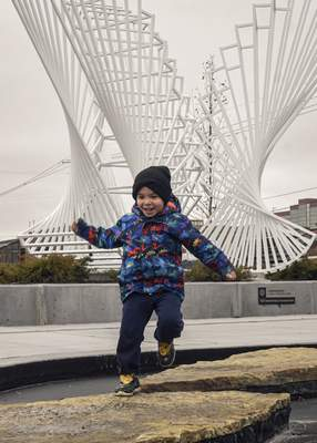 Mike Moore | The Journal Gazette Leo Dowling, 4, leaps across rocks Monday while walking with his grandfather and little brother at Promenade Park.