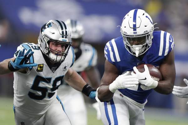 Indianapolis Colts running back Marlon Mack (25) runs past Carolina Panthers' Luke Kuechly (59) during the first half of an NFL football game, Sunday, Dec. 22, 2019, in Indianapolis. (AP Photo/Michael Conroy)