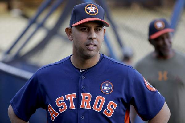 FILE - In this Oct. 23, 2017, file photo, Houston Astros bench coach Alex Cora watches batting practice during media day for baseball's World Series against the Los Angeles Dodgers, in Los Angeles. Houston manager AJ Hinch and general manager Jeff Luhnow were suspended for the entire season Monday, Jan. 13, 2020, and the team was fined $5 million for sign-stealing by the team in 2017 and 2018 season. Commissioner Rob Manfred announced the discipline and strongly hinted that current Boston manager Alex Cora â€