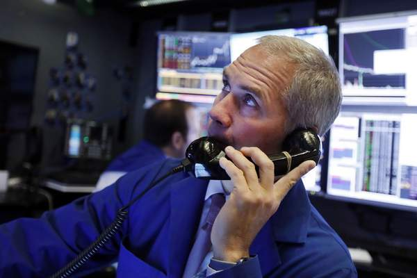 FILE - In this Jan. 9, 2020, file photo trader Timothy Nick works in his booth on the floor of the New York Stock Exchange. (AP Photo/Richard Drew, File)