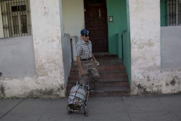 Alberto Perez, a 77-year-old retired man, leaves his home in the Sevillano neighborhood with an empty cooking gas tank as he departs for a shop where he will replace it with a full one in Havana, Cuba, Tuesday, Jan 14, 2020. (AP Photo/Ismael Francisco)