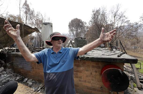 Colin Brennan stands in the debris of his destroyed house lost in the New Year's Eve wildfire at Nerrigundah, Australia, Monday, Jan. 13, 2020. (AP Photo/Rick Rycroft)