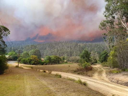 In this Dec. 30, 2019, photo provided by Siobhan Threlfall, a fire approaches the village of Nerrigundah, Australia. (AP Photo/Siobhan Threlfall)