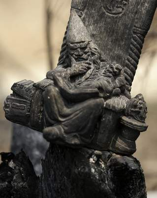 A blackened wizard ornament sits in a scorched fencepost at Nerrigundah, Australia, Monday, Jan. 13, 2020, after a wildfire ripped through the town on New Year's Eve. (AP Photo/Rick Rycroft)
