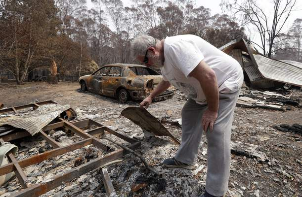 Lyle Stewart looks through burned debris at his destroyed house at Nerrigundah, Australia, Monday, Jan. 13, 2020, after a wildfire ripped through the town on New Year's Eve. (AP Photo/Rick Rycroft)