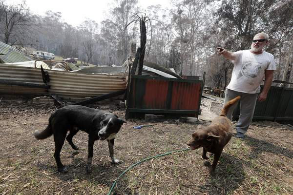 Lyle Stewart stands in front of his destroyed home at Nerrigundah, Australia, Monday, Jan. 13, 2020, after a wildfire ripped through the town on New Year's Eve. (AP Photo/Rick Rycroft)