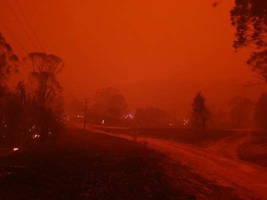 In this Dec. 31, 2019, photo provided by Siobhan Threlfall, fire and thick smoke remains the village of Nerrigundah, Australia. (AP Photo/Siobhan Threlfall)