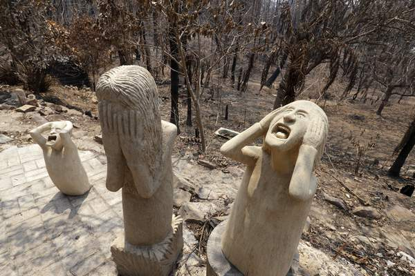 Sandstone sculptures by local fire captain Ron Threlfall show scenes of distress, Monday, Jan. 13, 2020, in Nerrigundah, Australia, that many residents of the town may have felt as a wildfire ripped through the town on New Year's Eve. (AP Photo/Rick Rycroft)
